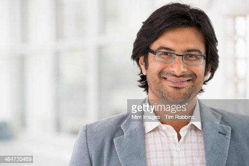 A business environment, a light airy city office. Business people. A man in a light jacket wearing glasses.