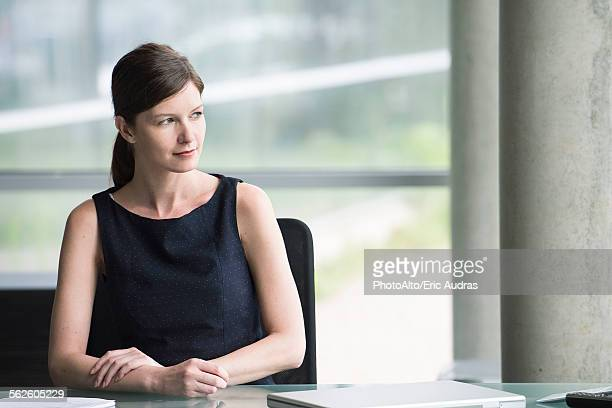 Business executive at desk looking away contemplatively