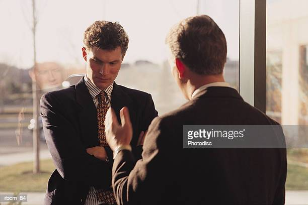 A business executive dressed in a suit confronts an employee and uses hand gestures as he talks