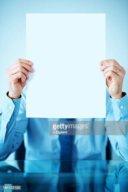 Business executive holds blank board in front of his face