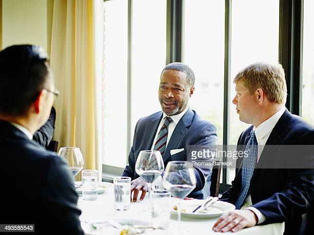Business executive leading lunch meeting