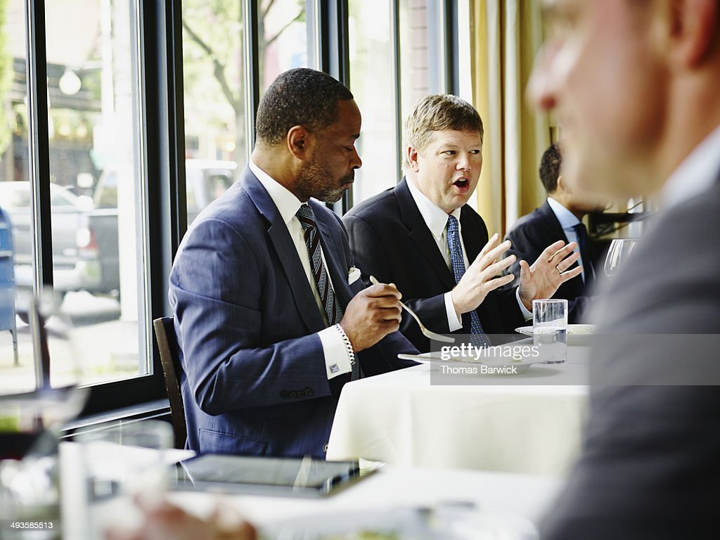 Business executive leading meeting in restaurant : Stock Photo