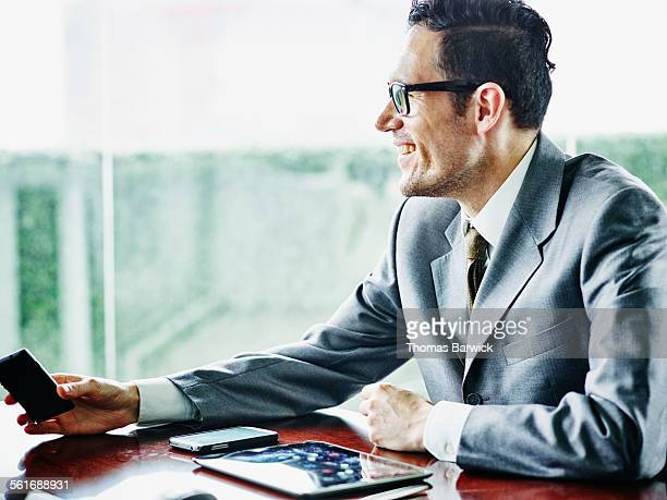 Business executive passing smartphone to colleague