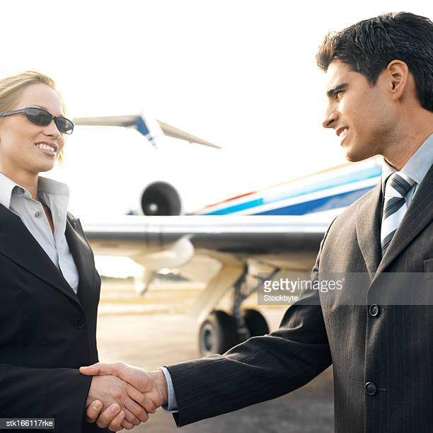 business executive shaking hands with a woman standing near an airplane at an airport