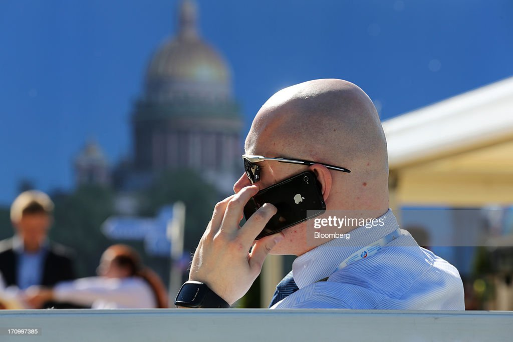 A business executive speaks on an Apple Inc. iPhone at a cafe terrace on the opening day of the St. Petersburg International Economic Forum 2013 (SPIEF) in St. Petersburg, Russia, on Thursday, June 20, 2013. Russian consumer spending probably eased and investment shrank at the fastest pace since 2011, adding to evidence the $2 trillion economy is stalling. Photographer: Andrey Rudakov/Bloomberg via Getty Images