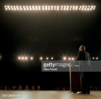 Business executive standing behind podium on stage : Stock Photo