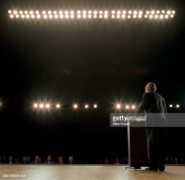 Business executive standing behind podium on stage