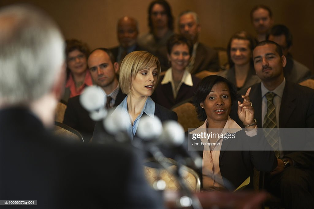 Business executives at conference room, focus on woman with hand raised