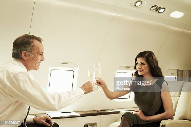 Business executives celebrating on private jet