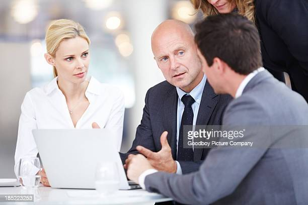 Business executives discussing ideas around table