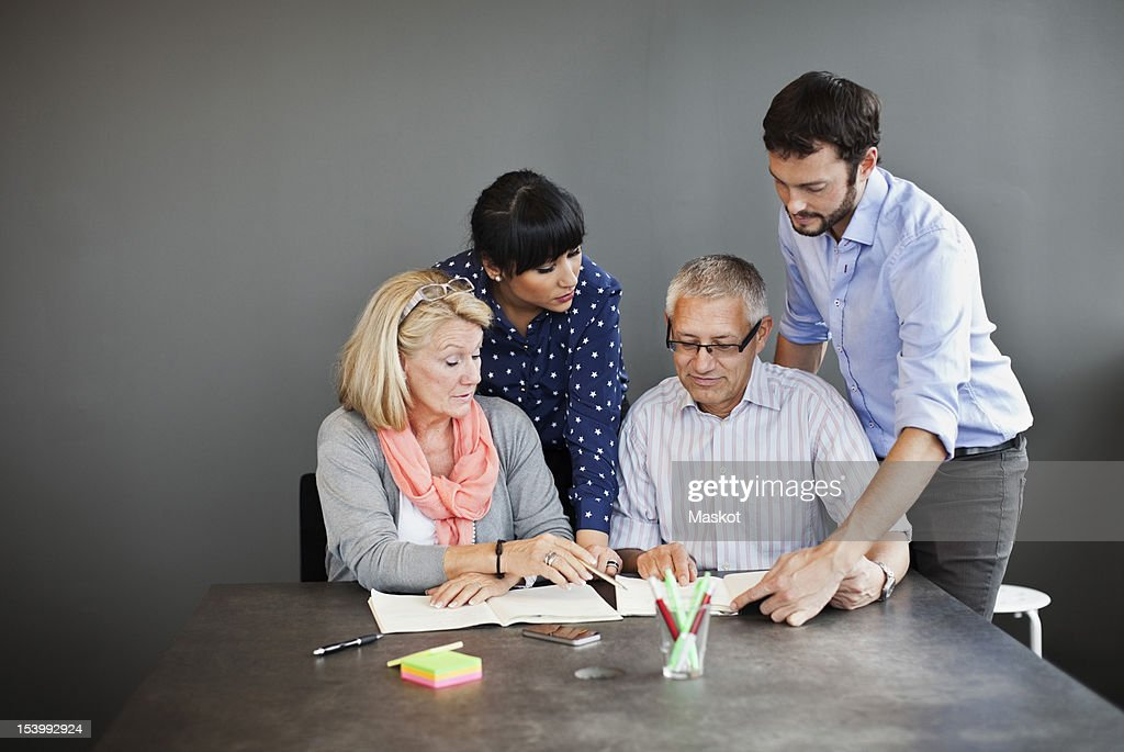 Business executives discussing on a document in office : Stock Photo