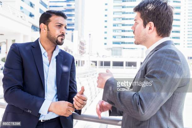 Business executives having a serious conversation outside their office