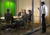 Business executives in meeting, man interrupting  with knock on glass