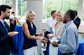 Business executives interacting with each other while having coffee at conference center
