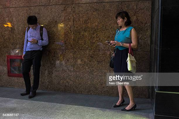 Business executives listening to music on their cellphones after work while waiting for their transport home in the CBD of Singapore
