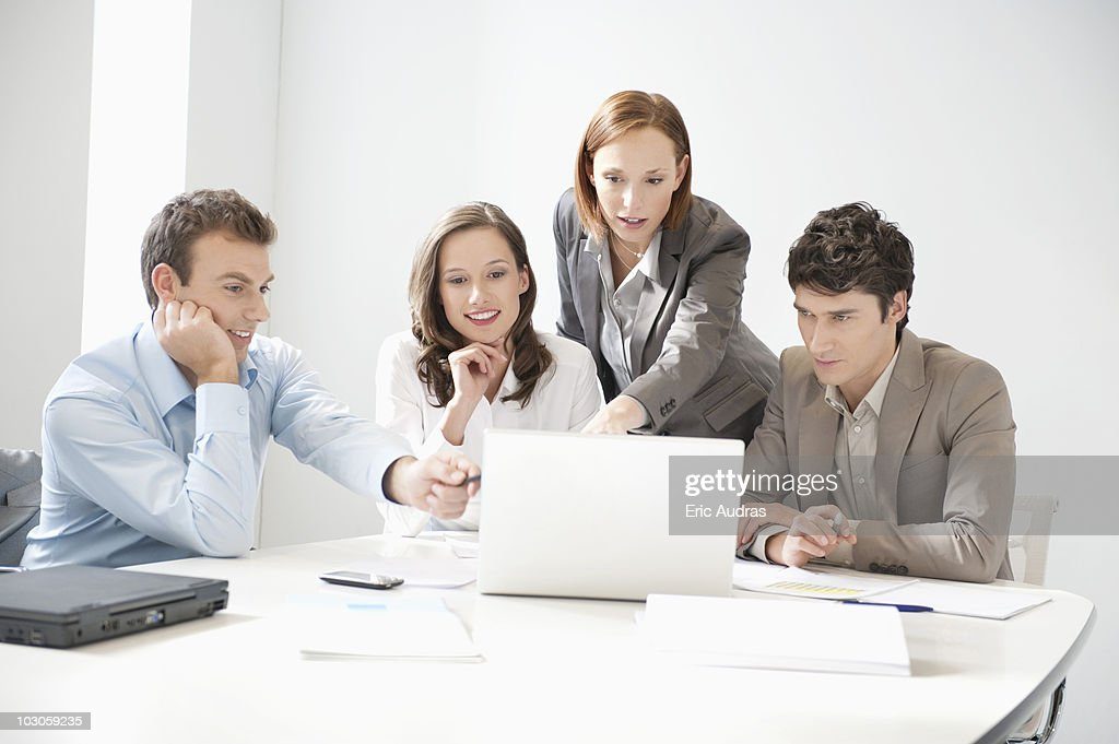 Business executives looking at a laptop in a board room : Stock Photo