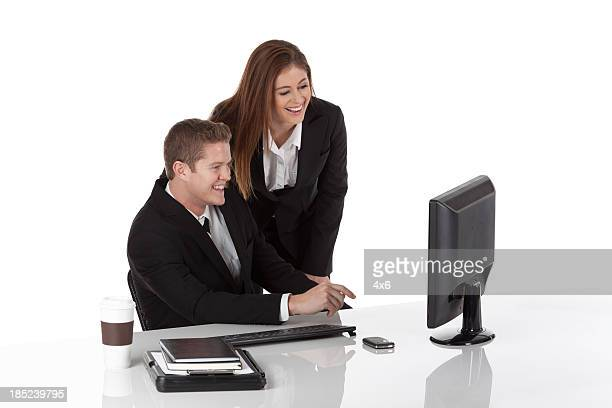 Business executives looking at computer and smiling