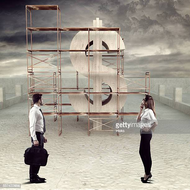 Business executives looking at under construction dollar sign
