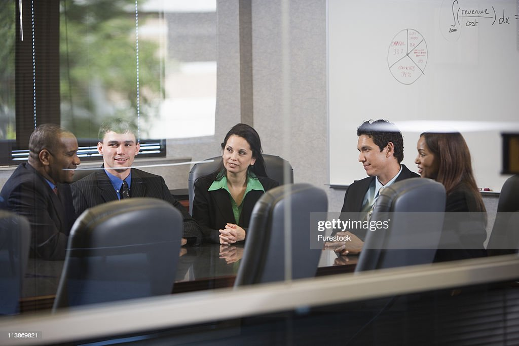 Business executives meeting in a conference room viewed through a window : Stock Photo