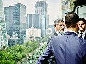 Business executives on terrace overlooking city
