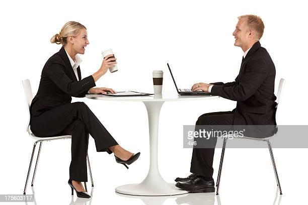 Business Manager gegenüber anderen sitzt auf einem Tisch