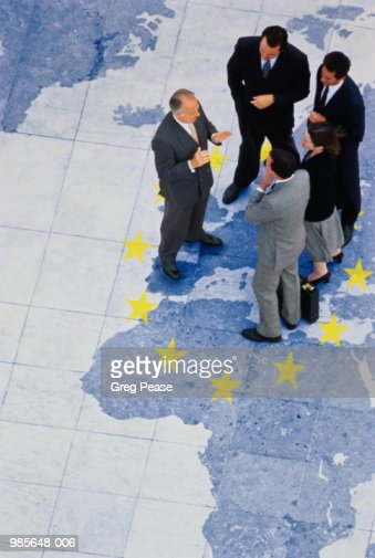 Business executives standing on world map, elevated view : Stock Photo