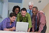 Business executives using a laptop and smiling