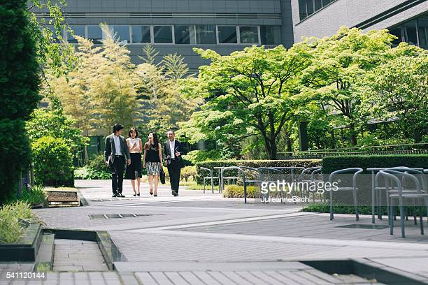 Business executives walking through office garden
