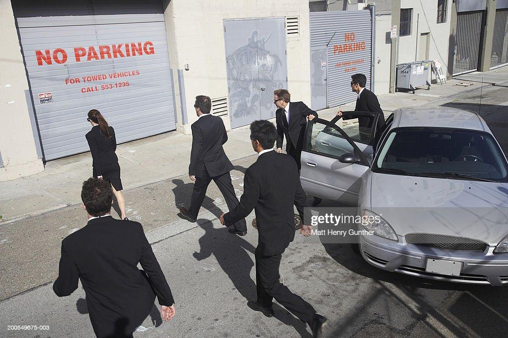 Business executives walking towards sidewalk : Stock Photo