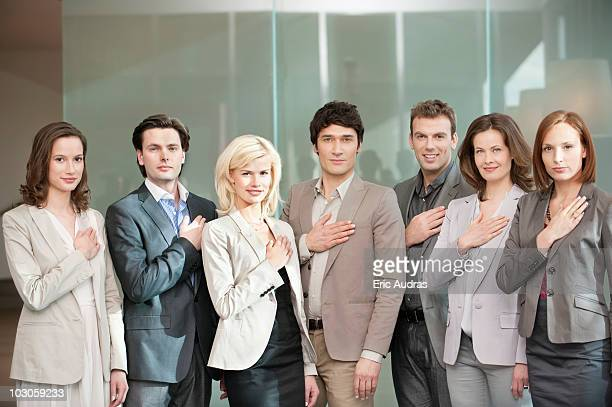 Business executives with their hands on their chest