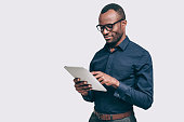Handsome young African man working on digital tablet while standing against grey background