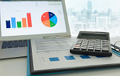Financial planning accounting concept. Calculator on business and financial report on desk of entrepreneur.