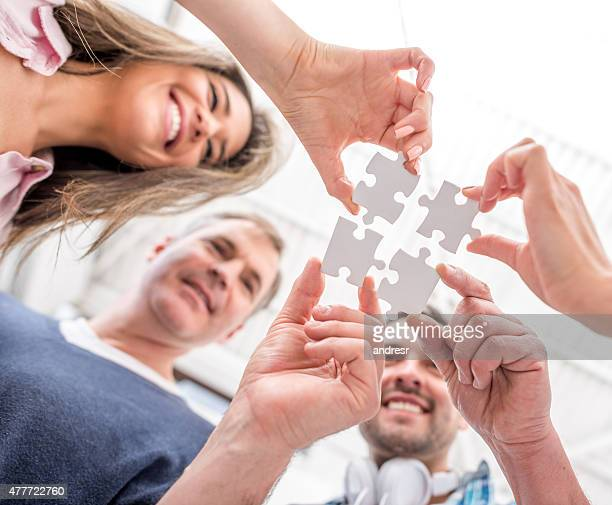 Business group assembling a jigsaw puzzle