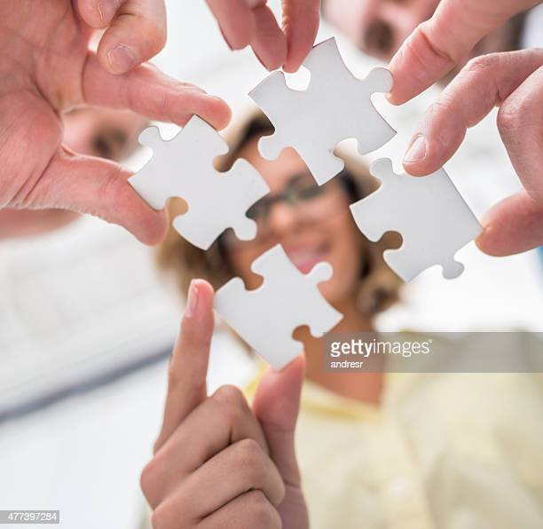 Business group assemling pieces of a puzzle together