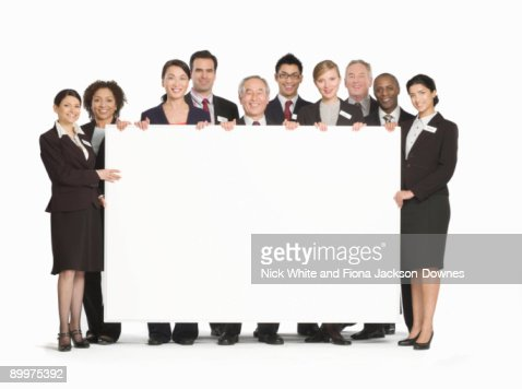 A business group holding a white board : Stock Photo
