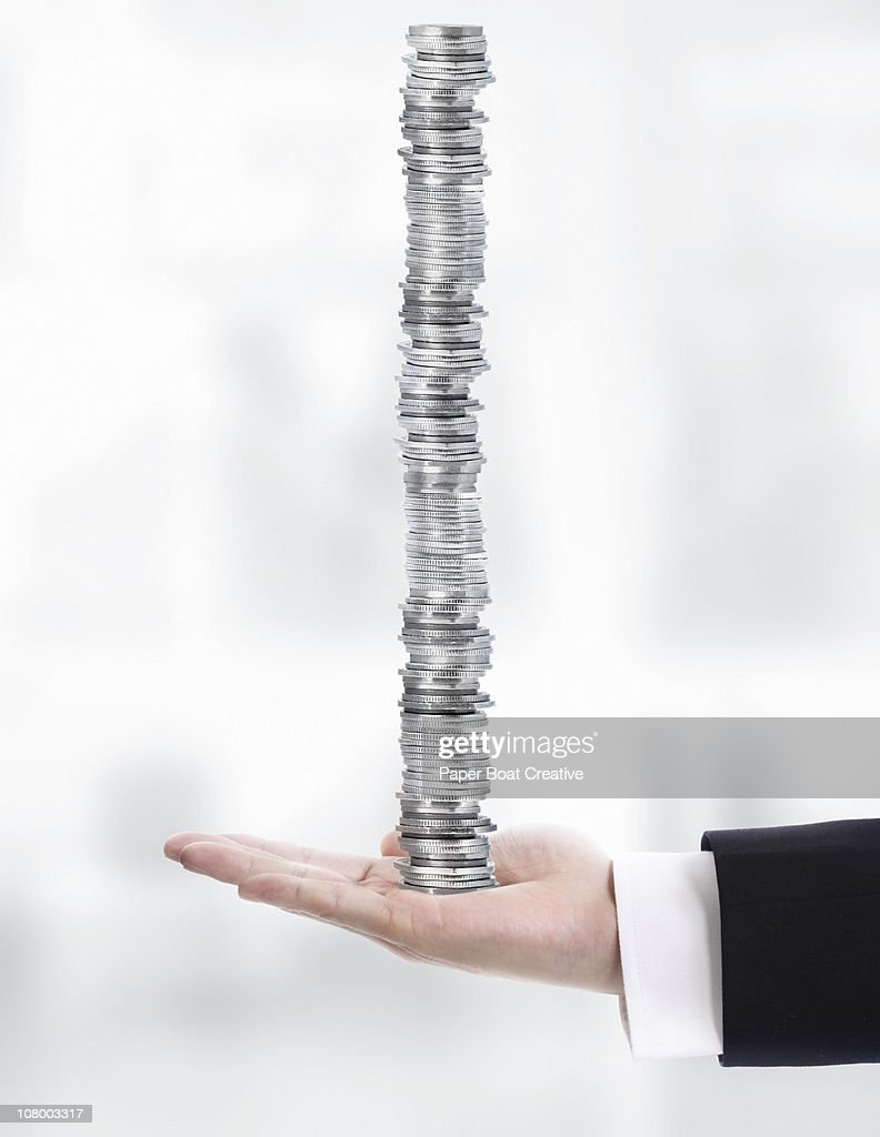 Business hand carrying a very high stack of coins : Stock Photo