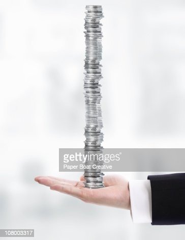 Business hand carrying a very high stack of coins : Foto de stock