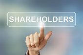business hand pushing shareholders button on blurred background