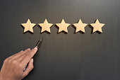 Business hand select five star rating on wooden. concept customer service excellent