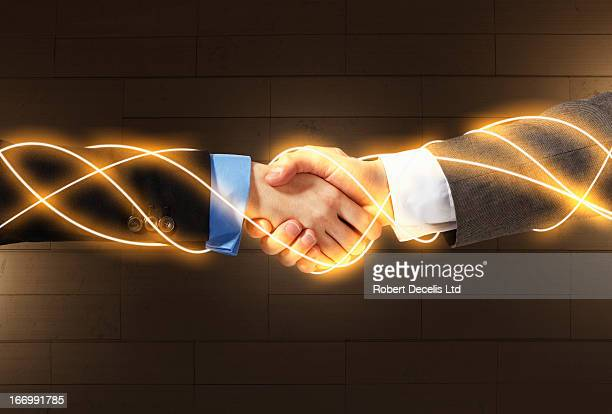Business hand shake connected by light trails