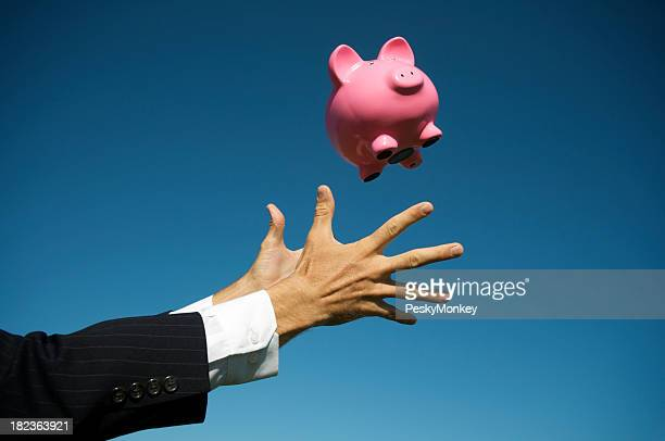 Business Hands Reach Out to Catch Piggy Bank