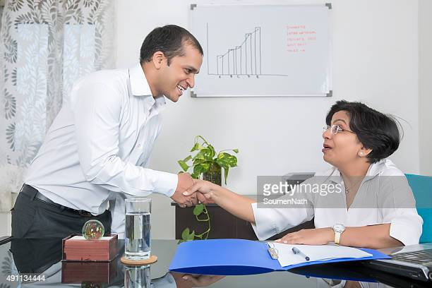 Business handshake. Businessman and businesswoman shaking hands with each other.