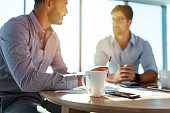 Business executives discussing work at office. Closeup of coffee cup with blurred image of two businessmen sitting on table.