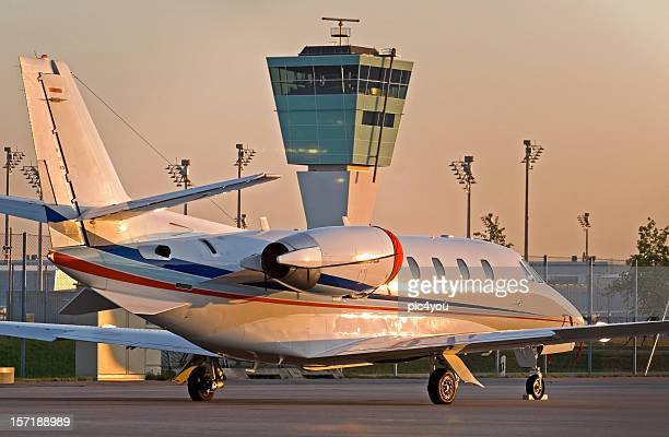 Business jet parked in front of the control tower