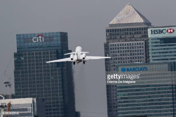 A business jet takes off from the London City Airport LCY and climbs over Canary Wharf financial district on April 20 2017 in London England