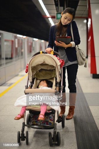 Business lady talking on mobile pushing stroller : Stock Photo