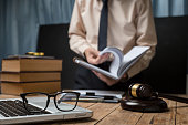 Business lawyer working hard at office desk workplace with book and documents.