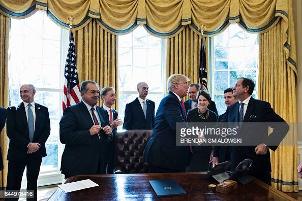 Business leaders congratulate US President Donald Trump after signing an executive order about regulatory reform in the Oval Office of the White...