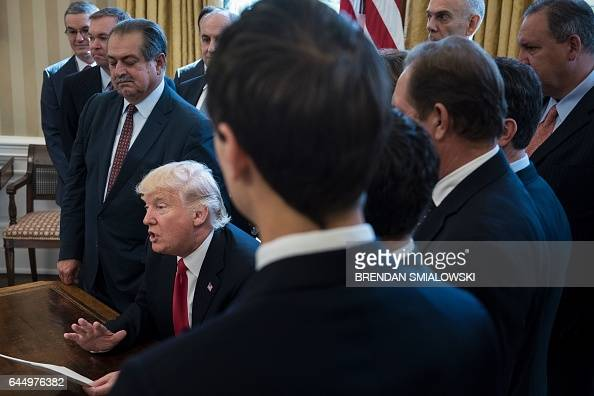 Business leaders listen as US President Donald Trump speaks to the press about an executive order on regulatory reform in the Oval Office of the...