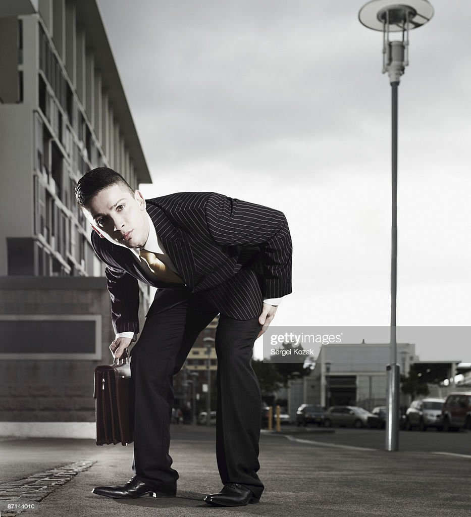Business male, bending over to see the camera